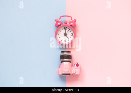 Flat lay of dslr camera toy and small alarm clock on pastel background minimal creative concept. - Stock Photo
