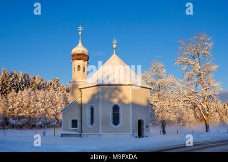 Snow-covered Nikolauskapelle in the morning light, Geretsried, Upper Bavaria, Bavaria, Germany - Stock Photo