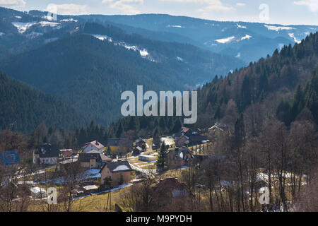 Upper parts of Piwniczna Zdroj village with Beskid Sadecki mountains and forests in the background on a sunny day. - Stock Photo