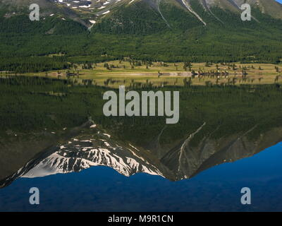 Khoton Lake with green forest landscape and water reflection of snow-covered mountains, Mongolia - Stock Photo