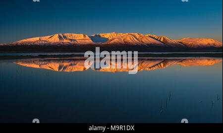 Khoton Lake, snow-covered mountains with dawn in the back, Mongolia - Stock Photo
