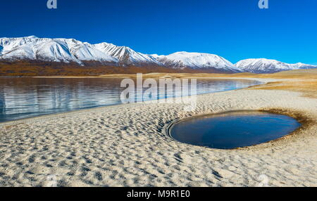 Sandy beach with pool, Khoton Lake, snow-covered mountains in the back, Mongolia - Stock Photo