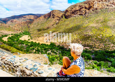 Senior woman enjoying the view of the Huisrivierpas, between Ladismith and Calitzdorp in the Little Karoo of the Western Cape Province of South Africa - Stock Photo