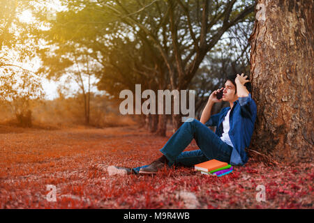 young man in stress situation when talking on mobile phone in the park - Stock Photo