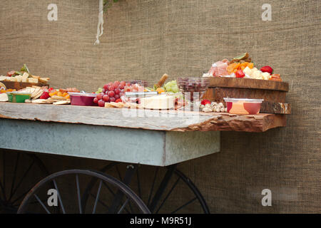 A bright & colorful selection of fruit, nuts, cheeses, dips, Deli meats and crackers spread across a beautiful slab of wood. - Stock Photo