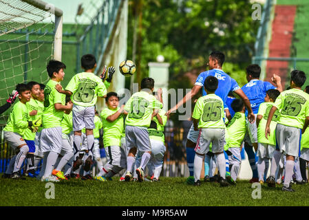 Five players of Indonesian football club of Persib Bandung play against 85 children in an exhibition match to celebrate its 85th anniversary. - Stock Photo
