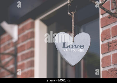 Decorative heart hanging on the wall outside of brick house. Love cozy home concept - Stock Photo