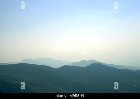 Layer of mountain peaks covered with coniferous deciduous forest in the morning,Morning mountain landscape with waves of fog . - Stock Photo