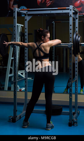Woman with the barbell in the gym  - Stock Photo