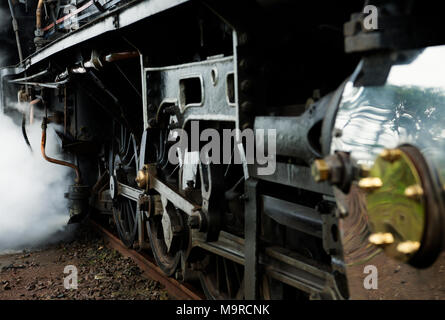 Close up detail of steam engine drive wheels and working parts on operational vintage locomotive - Stock Photo