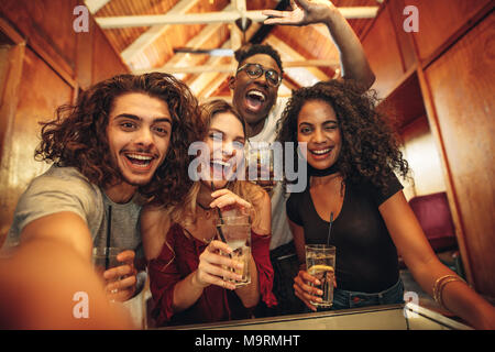 Group of happy young friends with drinks gathered for party in club. Excited men and woman with drinks taking selfie during party. - Stock Photo