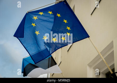 Eu, European Union, flag with flag of Estonia behind it  waiving in the city. - Stock Photo