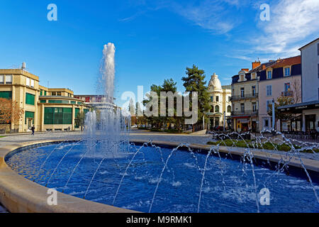 Europe, France, Auvergne, Vichy, Place Charles de Gaulle, fountain, Place Charles de Gaulle, post, postal bank, architecture, trees, buildings, people - Stock Photo