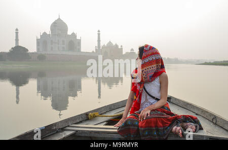 An Asian woman watching sunset over Taj Mahal from a wooden boat. - Stock Photo