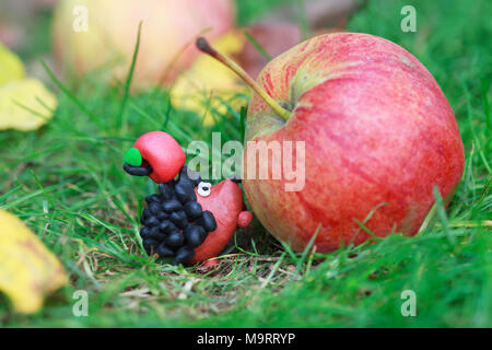Plasticine world - small homemade hedgehog with red apple on his back is trying to climb to the big apple, selective focus on the hedgehog - Stock Photo