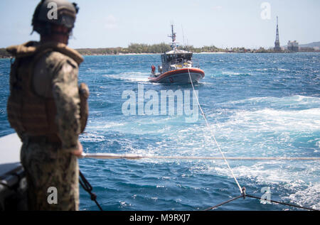 A Sailor assigned to Coastal Riverine Squadron (CRS) 4, Det. Guam watches as a Mark VI patrol boat tows a 47-foot Motor Lifeboat assigned to U.S. Coast Guard Sector Guam during a towing exercise in Apra Harbor, Guam, March 28, 2018. CRS-4, Det. Guam is assigned to Commander, Task Force 75, the primary expeditionary task force responsible for planning and execution of coastal riverine operations, explosive ordnance disposal, diving engineering and construction, and underwater construction in the U.S. 7th Fleet area of operations. (U.S. Navy Combat Camera photo by Mass Communication Specialist 1 - Stock Photo
