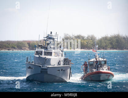 Sailors assigned to Coastal Riverine Squadron (CRS) 4, Det. Guam reach for a line from U.S. Coast Guard Sailors aboard a 47-foot Motor Lifeboat, assigned to U.S. Coast Guard Sector Guam, during a towing exercise in Apra Harbor, Guam, March 28, 2018. CRS-4, Det. Guam is assigned to Commander, Task Force 75, the primary expeditionary task force responsible for planning and execution of coastal riverine operations, explosive ordnance disposal, diving engineering and construction, and underwater construction in the U.S. 7th Fleet area of operations. (U.S. Navy Combat Camera photo by Mass Communica - Stock Photo