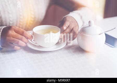 Close up of female hands touching white cup - Stock Photo