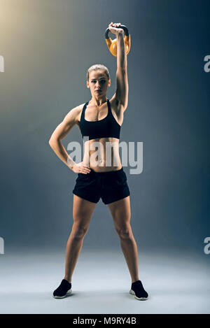 Strong female athlete swinging kettlebell while exercising - Stock Photo