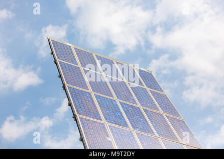 Pole with 20 solar panels collecting sunlight in a blue sky. - Stock Photo
