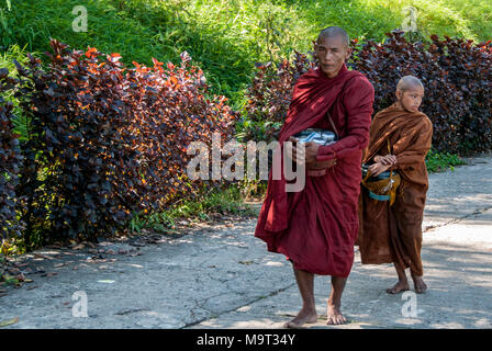 a monk ascends to the Golden Rock Pagoda followed by his disciple - Stock Photo