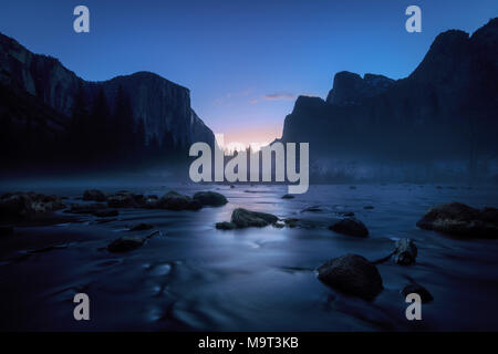 Misty blue sunrise over granite cliffs and the Merced River in Yosemite National Park - Stock Photo