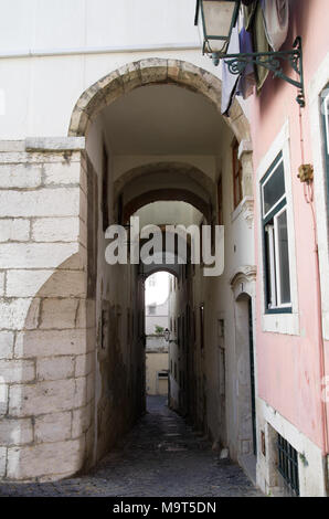 Narrow and sloped cobblestone street under a tall archway in Alfama disctrict, the most famous and ancient typical neighborhood of Lisbon. Portugal. - Stock Photo