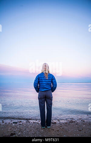 A woman standing at waters edge at sunset seen from behind. - Stock Photo