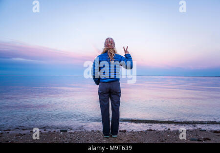 A woman standing at waters edge making a peace sign with her hand / fingers. - Stock Photo