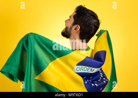 Brazilian soccer football team player. One supporter and fan holding Brazil flag. Wearing yellow uniform on yellow backdrop. - Stock Photo