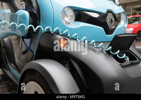 STUTTGART, GERMANY - SEPTEMBER 12 2017; Bright blue and black micro-car Renault Twizy recharging on city street plugged in with extendable cable - Stock Photo