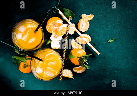 refreshing cocktail with tangerines, juice and ice in two glasses on a black background, alcoholic drink, copy space - Stock Photo