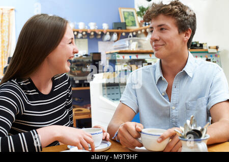 Teenage Couple Meeting In Cafe And Drinking Cup Of Coffee - Stock Photo
