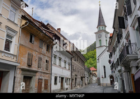 Street A small town in the mountains of Slovenia, Europe. Shabby old houses facades, and roofs. Center of the city and the Catholic Church - Stock Photo