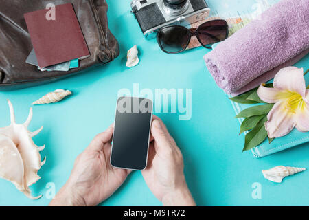 Travel concept. Female hands with smartphone. Packing things and summer accessories for a trip on punchy pastel blue background. View from above. Clos - Stock Photo
