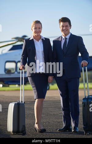 Portrait Of Businessman And Businesswoman Standing In Front Of Helicopter - Stock Photo