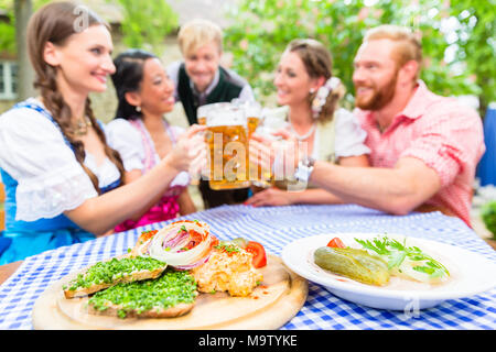 Friends in beer garden with drink and Bavarian appetizers - Stock Photo