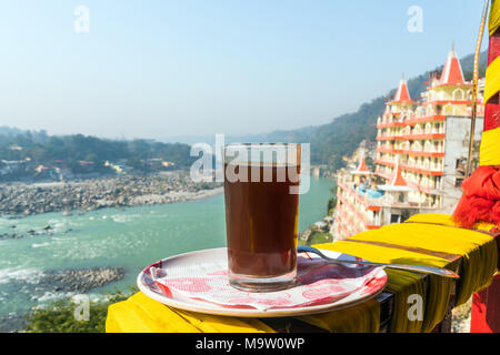 A Cup of coffee on a beautiful background of the city Rishikesh. Tourist Indian Breakfast at early morning in the Himalayan mountains. - Stock Photo
