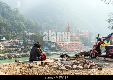 poor man sits on the banks of the Ganges river and looks towards the temple Tera Manzil Temple. Morning prayer before the Holy place. Meditation in Ri - Stock Photo