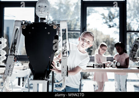 Cute youngster getting excited while embracing robotic machine - Stock Photo