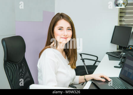 Portrait of skilled administrative manager working on laptop computer in office satisfied with occupation, young female receptionist organizing workin - Stock Photo