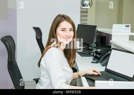 Portrait of smiling skilled administrative manager working on laptop with white empty screen in office satisfied with occupation, young female recepti - Stock Photo
