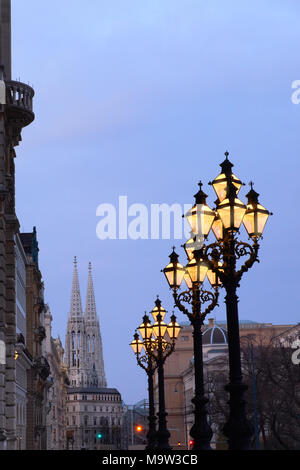Ornate historical lamp posts outside Rathaus Vienna, or Vienna Town Hall in the evening. Votivkirche sphires are in the background. - Stock Photo