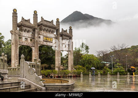 Po Lin Monastery Gate with the mist obscuring the mountain beyond. Located at Ngong Ping, Lantau Island, one of the Hong Kong Islands. - Stock Photo