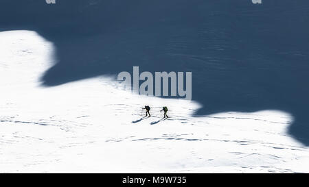 Ski mountaineers in the shadows of the mountains. Artistic style photo. - Stock Photo