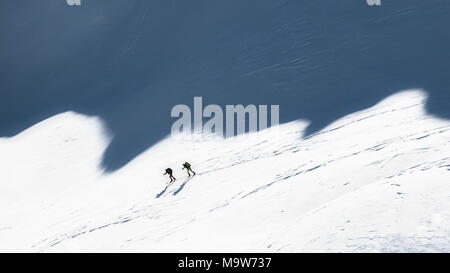 Ski mountaineers in the shadows of the mountains. - Stock Photo