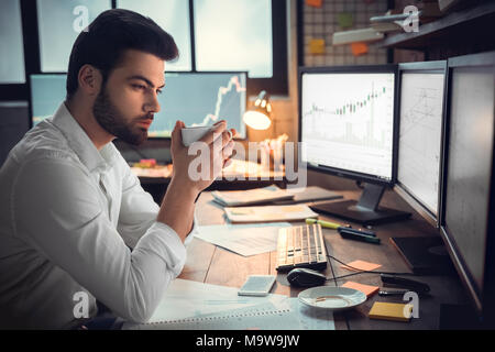 Thoughtful serious trader broker drinking coffee working overtime looking at computer monitors analyzing stock trading market graphs, overwork, lack o - Stock Photo