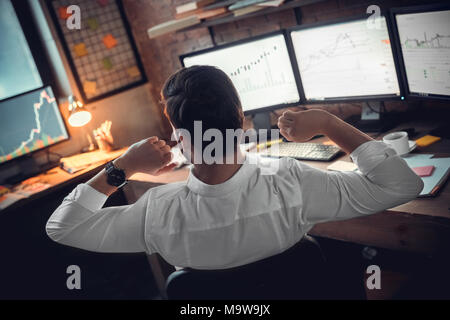 Rear view at stock trader broker or investor stretching hands at workplace tired after long using computer, businessman finished work taking break for - Stock Photo