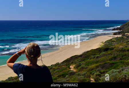 Woman looking north along  Yallingup beach towards Cape Naturaliste Lighthouse ,Yallingup, Western Australia - Stock Photo