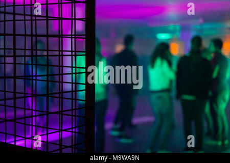 Group of unrecognizable young people dancing during a party in an improvised warehouse with boxes in the foreground - Stock Photo